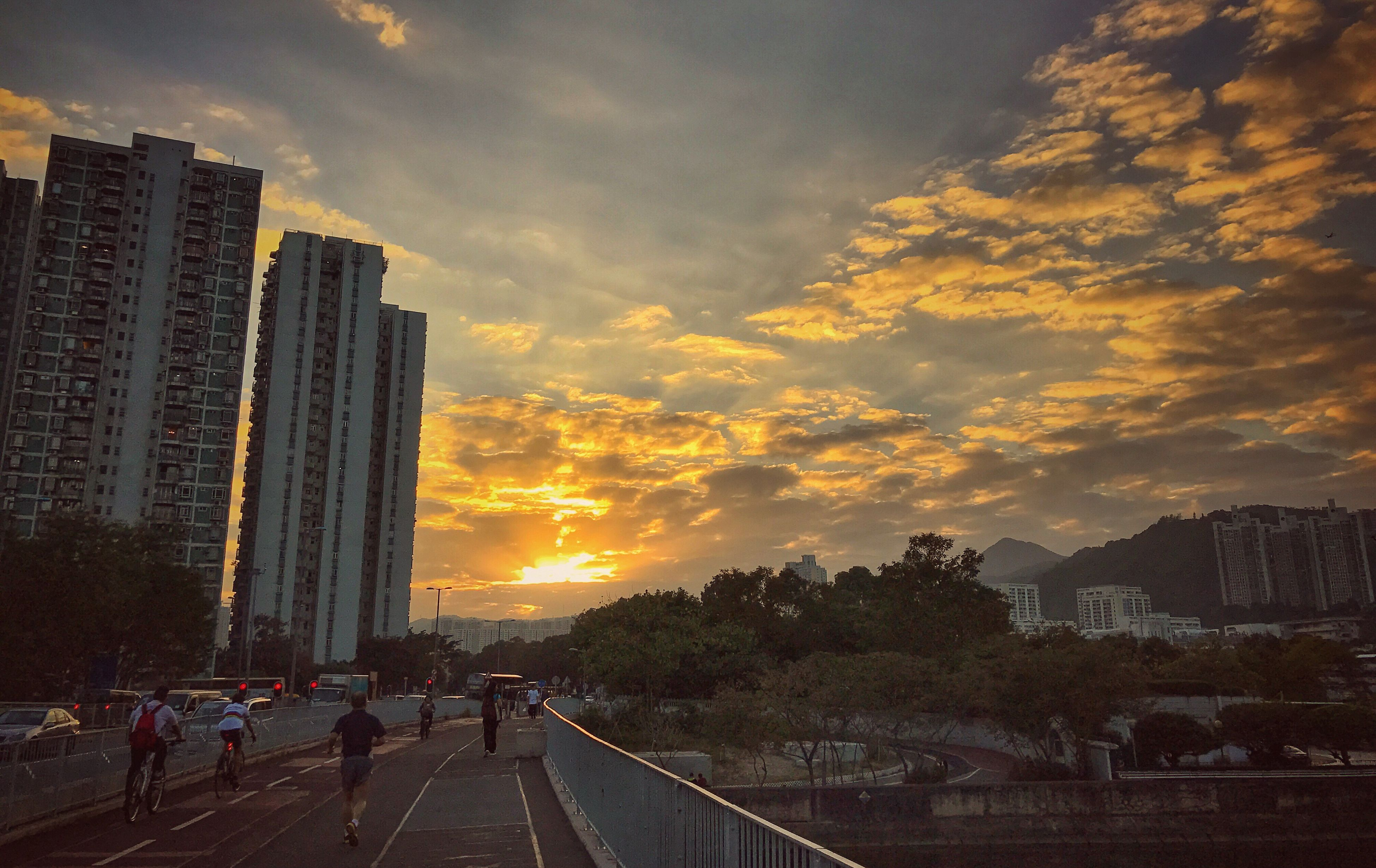 city, sunset, skyscraper, building exterior, architecture, cityscape, sky, built structure, cloud - sky, outdoors, travel destinations, transportation, city life, urban skyline, growth, development, tree, downtown district, no people, nature, day