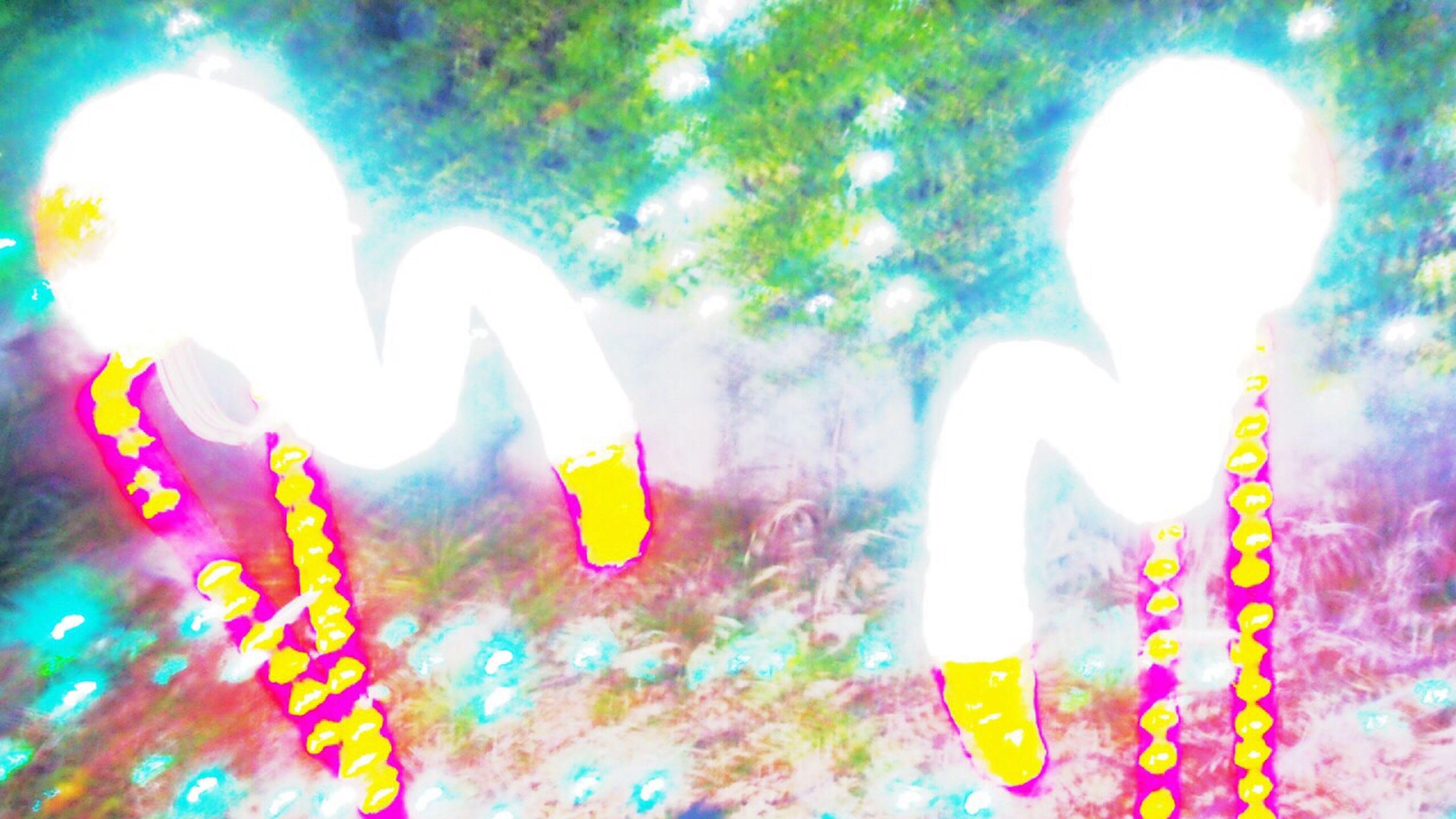 illuminated, low angle view, blue, human representation, lighting equipment, art, art and craft, creativity, lens flare, multi colored, indoors, decoration, close-up, celebration, light - natural phenomenon, sunlight, sky, green color