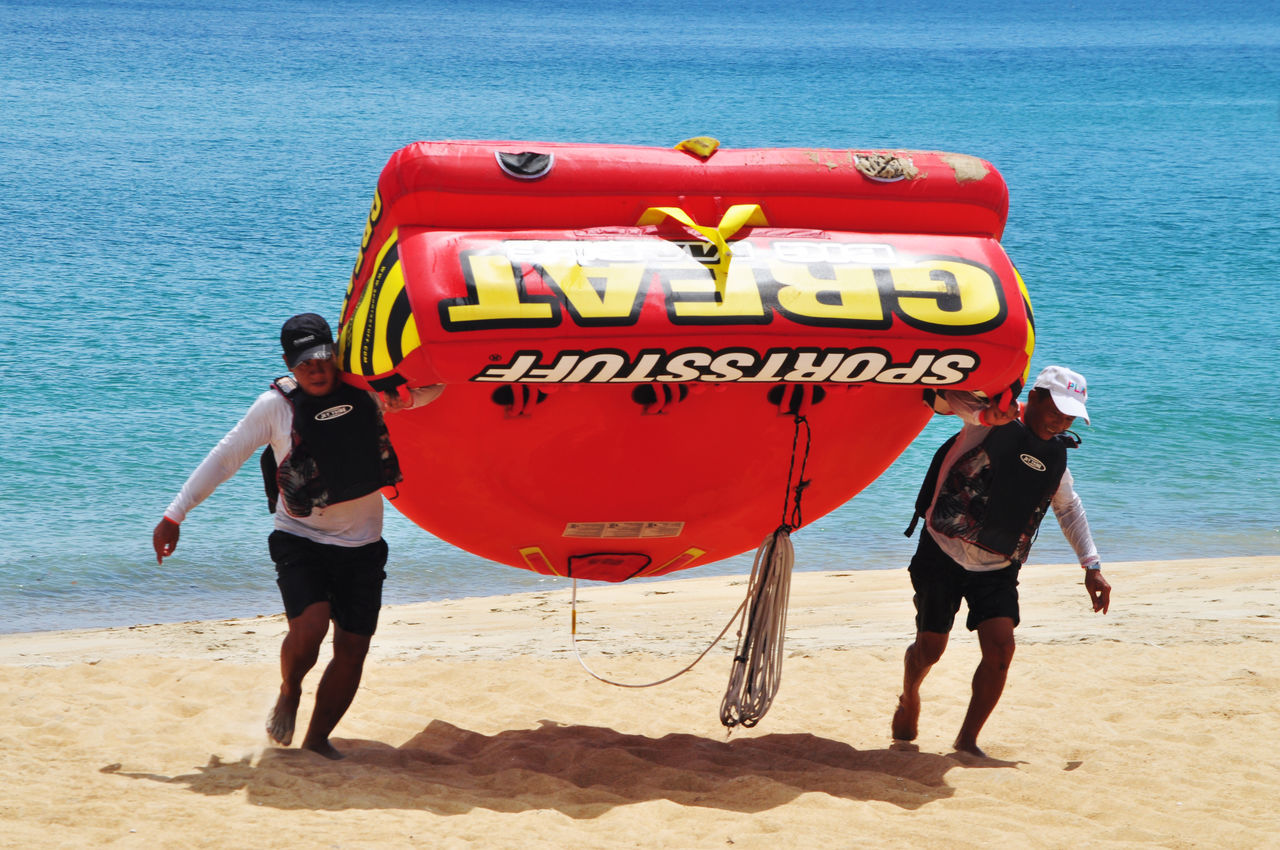 Resort staff carrying inflatable on beach at Lang Co, Vietnam. Activities Beach Beach Holiday Carrying Color Of Sport Editorial  Holidays Inflatables Lang Co Beach Resort Sand Sea Tourism Tourism Destination Travel Vacation Vacations Vietnam Water Western Script Working