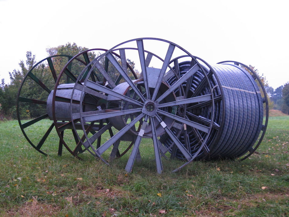 Big metal cable drums in the field Cable Cable Drum Communication Connection Construction Drum Electricity  Electricity Wires Fiber Field Grass Industry Internet LINE Metal Nature No People Outdoors Power Reel Roll Rural Scene Spool Technology Wire