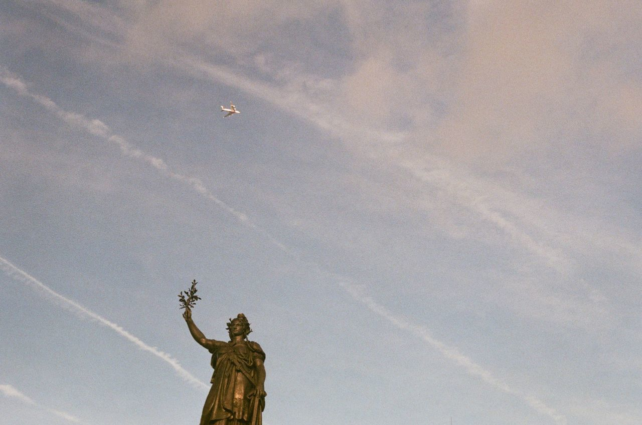 low angle view, statue, vapor trail, human representation, sculpture, sky, flying, day, outdoors, no people, airplane, contrail