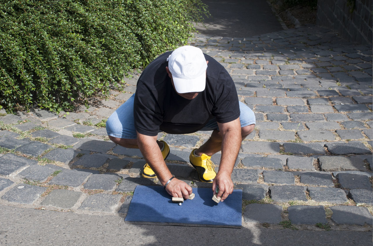 An illegal shell game player. The shell game (also known as thimblerig, three shells and a pea, the old army game. Adult Adults Only Men One Man Only One Person Only Men Outdoors People Shell Game