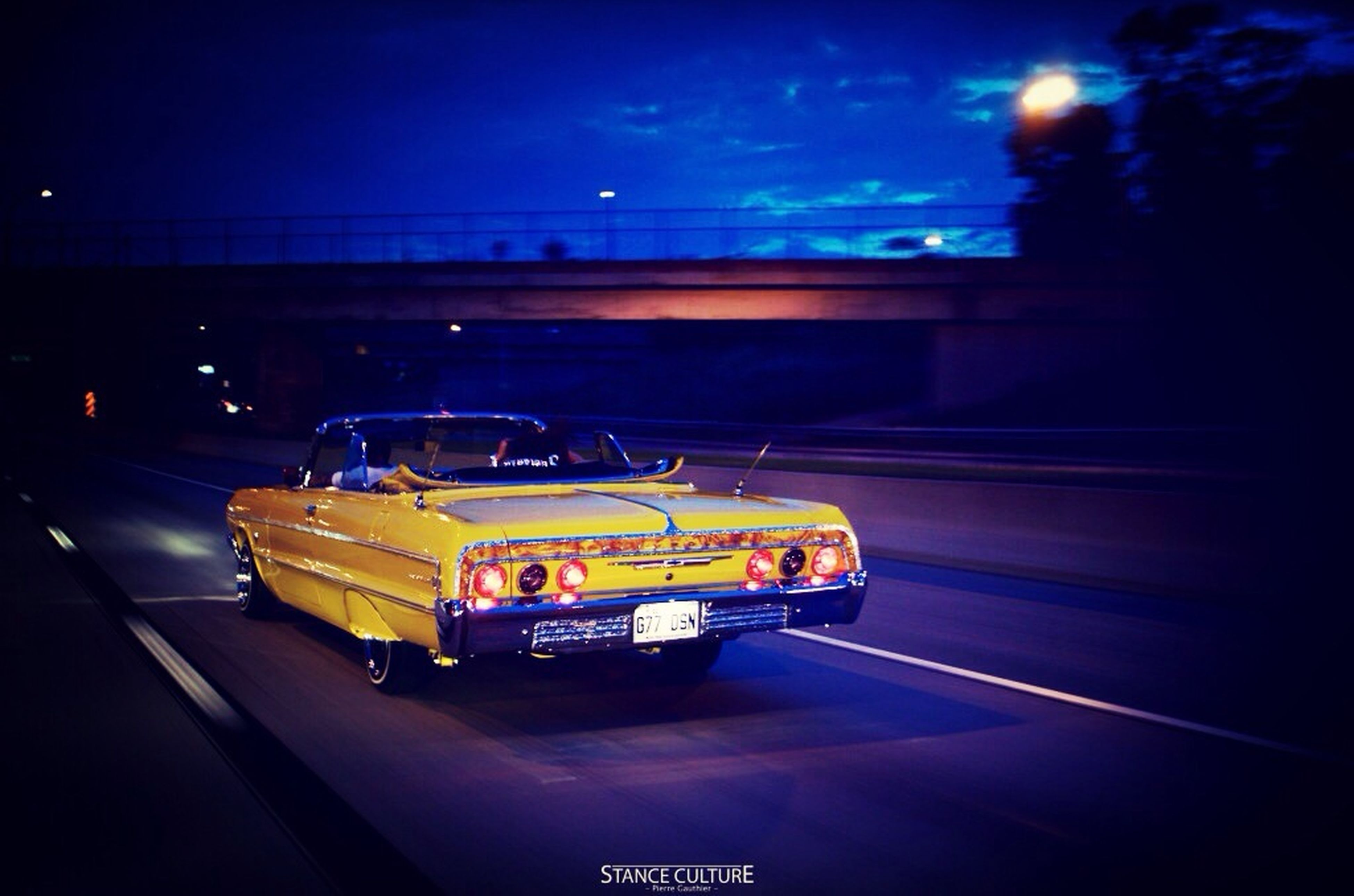 transportation, mode of transport, car, land vehicle, night, illuminated, on the move, traffic, road, street, motion, travel, sky, speed, city, outdoors, yellow, no people, vehicle, built structure