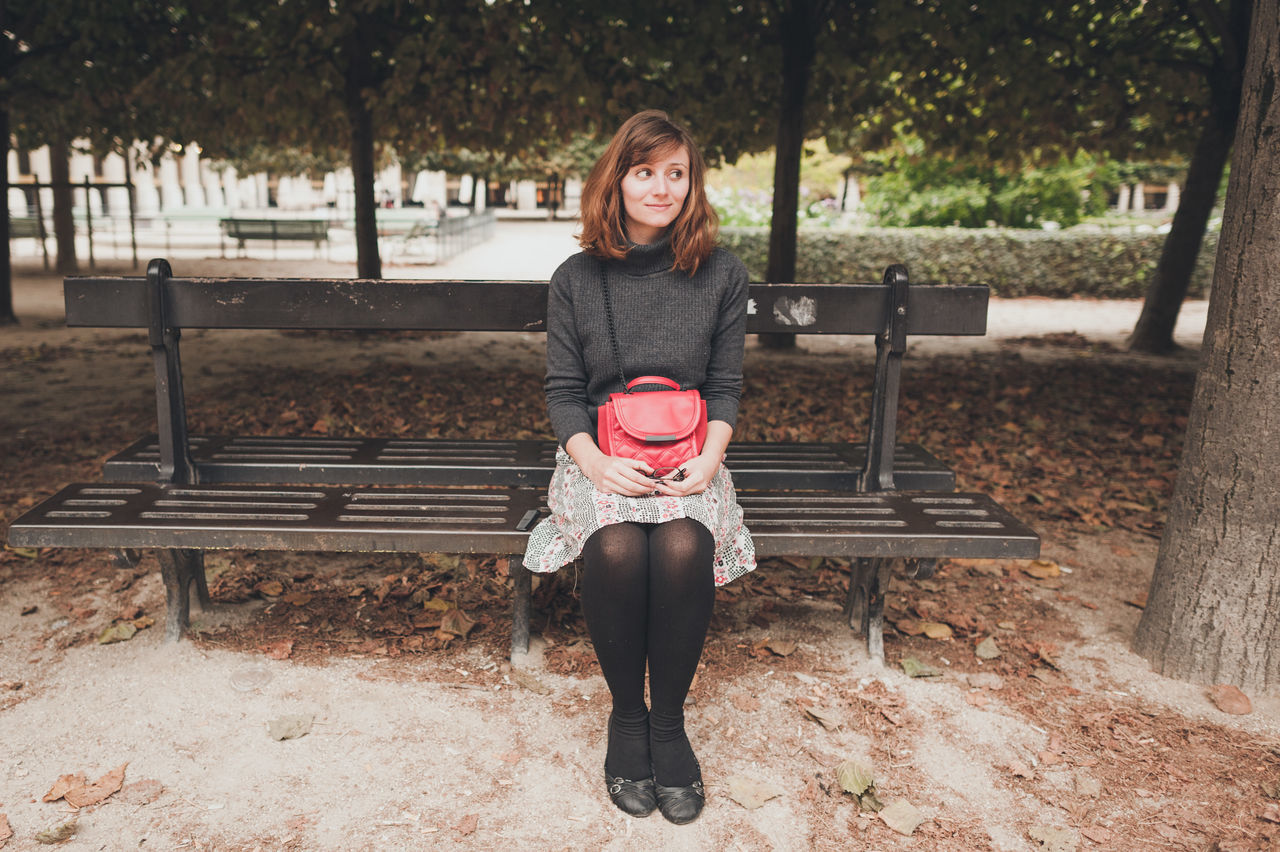 Beautiful Woman Holding Bag And Sitting On Bench At Park