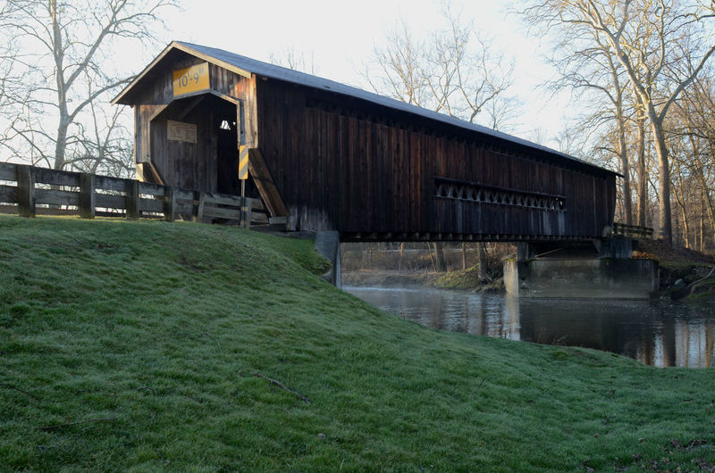 early morning sunlight on entrance to wooden covered bridge over river Architecture Bare Tree Building Exterior Built Structure County Road Covered Bridge Day Grass Green Grass Nature No People Outdoors Riverbank Rural America Rural Road Rural Scene Sky Tree Vintage Bridge Wooden Bridge Over Water