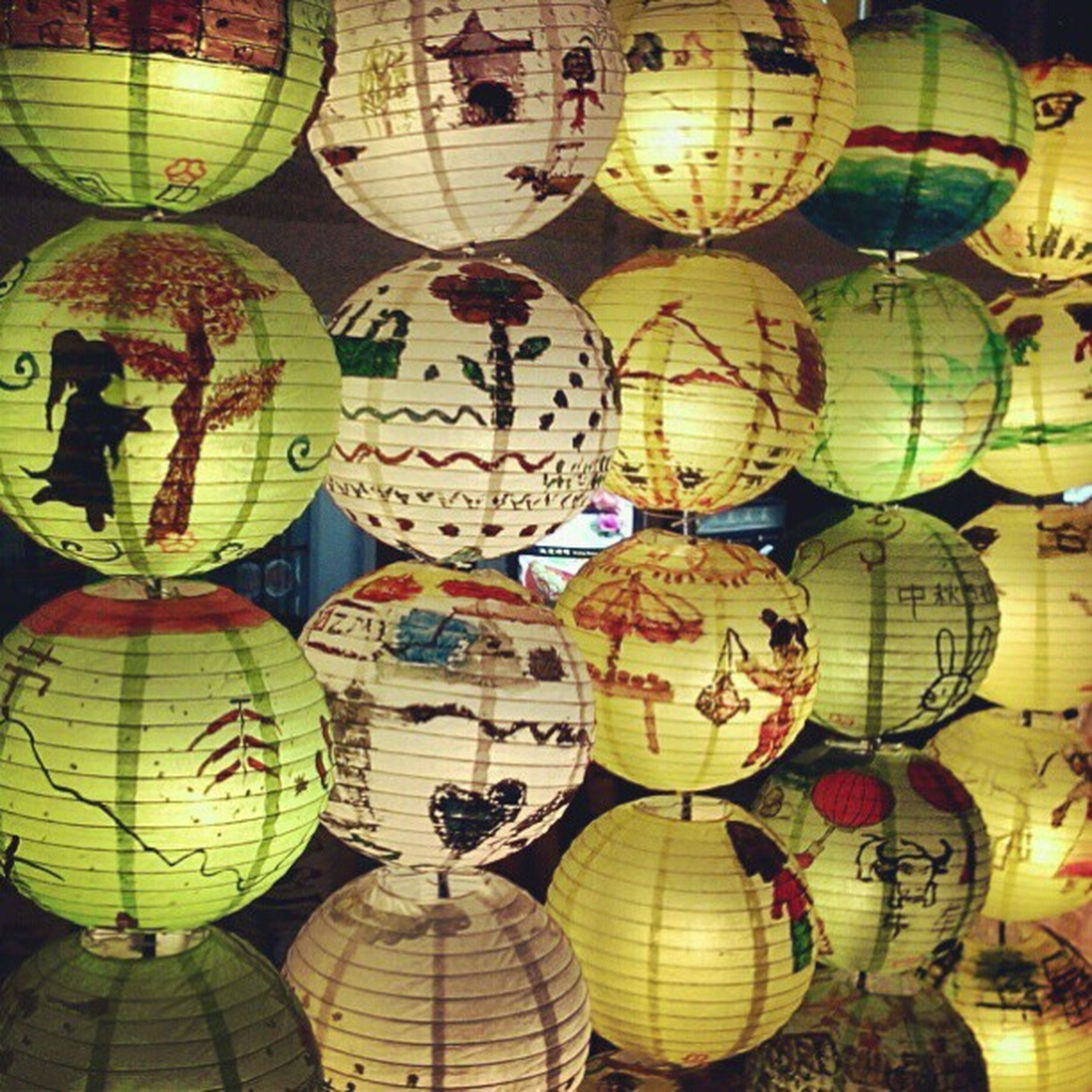 multi colored, art and craft, art, creativity, illuminated, decoration, indoors, cultures, lantern, arts culture and entertainment, tradition, variation, in a row, celebration, pattern, night, hanging, lighting equipment, design, circle