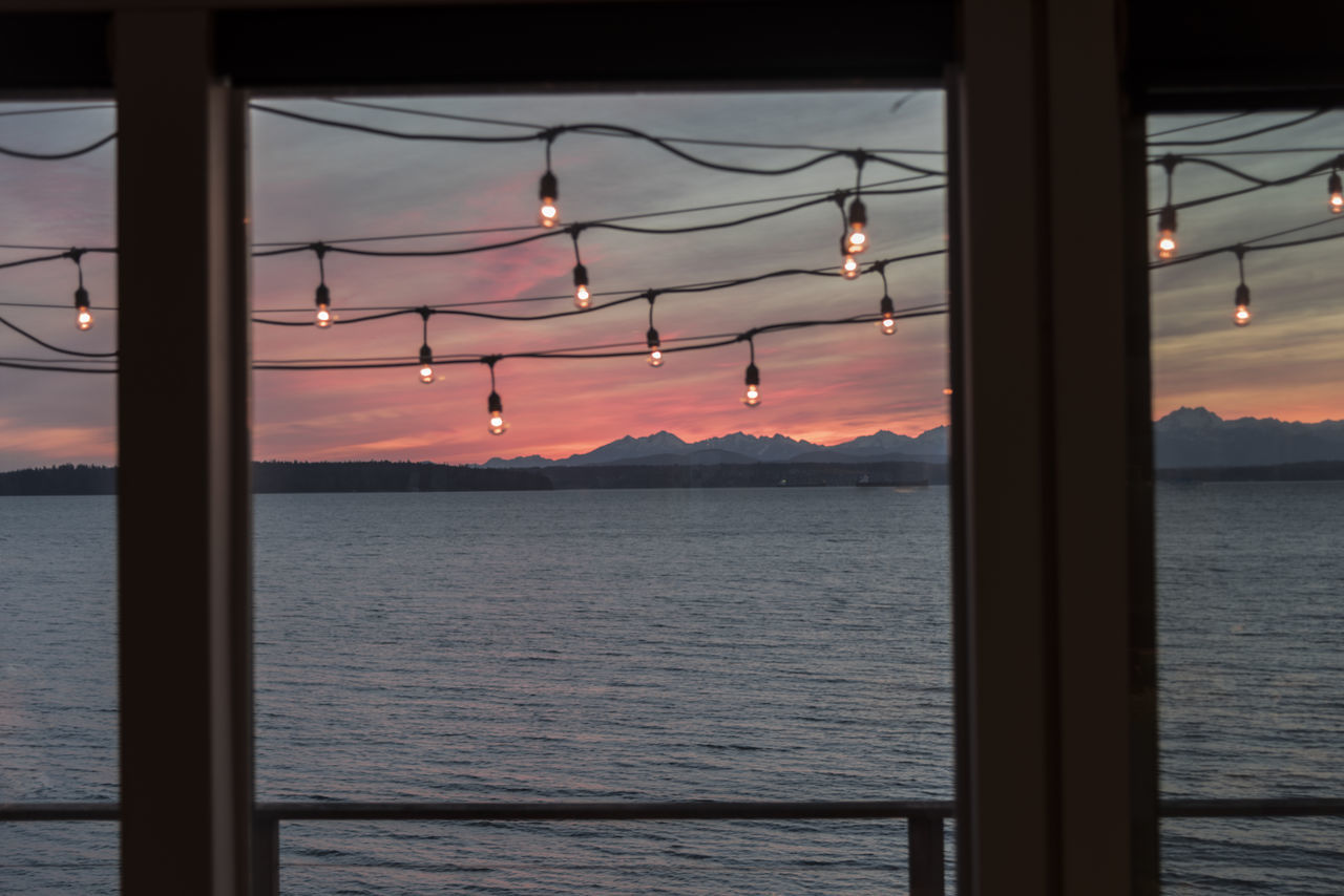 Sunset view of mountains and water at sunset from inside windows with hanging deck lights Beach Cabin Cruise Deck Decorating Design Evening Hanging Home House Interior Lights Orange Patio Pink Sailing Seascape Seaside Sky Sunset Travel Vacation Vibrant Color View Windows