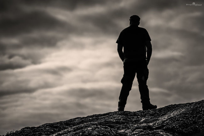 Mountaineer who enjoys the tranquility of arctic nature Black & White Silhouette Arctic Nature Autumn Fall Clouds Rock SkoglundFoto