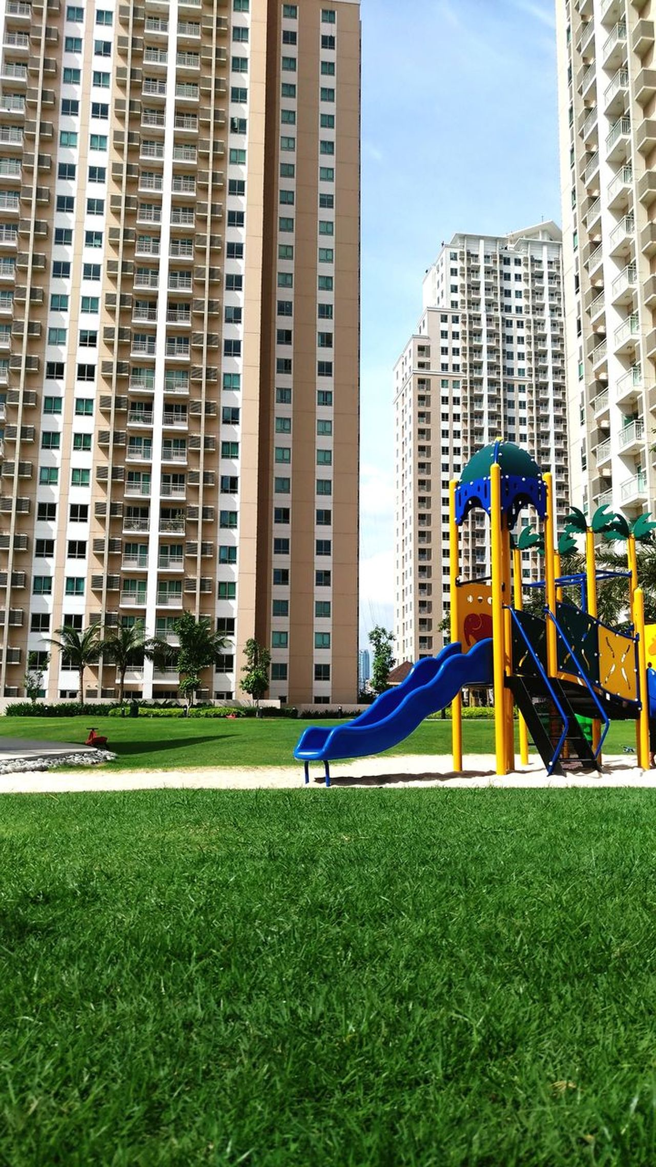 Grass Apartment Built Structure Playgrounds Playground Equipment Outdoors Morning Sun EyeEmNewHere Adapted To The City