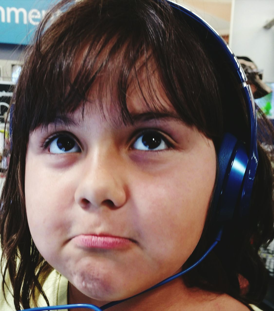 Close-Up Of Girl Listening To Music At Store
