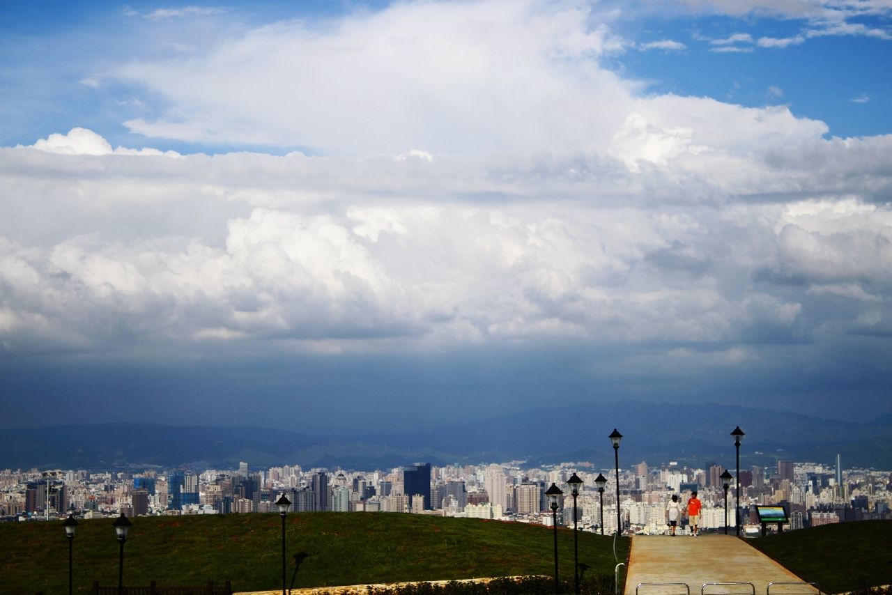 View of cityscape against cloudy sky
