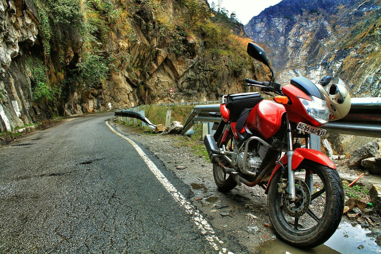 transportation, day, mountain, rock - object, land vehicle, outdoors, mode of transport, motorcycle, road, no people, stationary, nature, tree