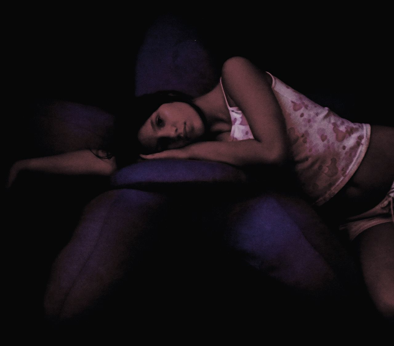 Portrait Of Young Woman Lying On Teddy Bear In Darkroom At Home