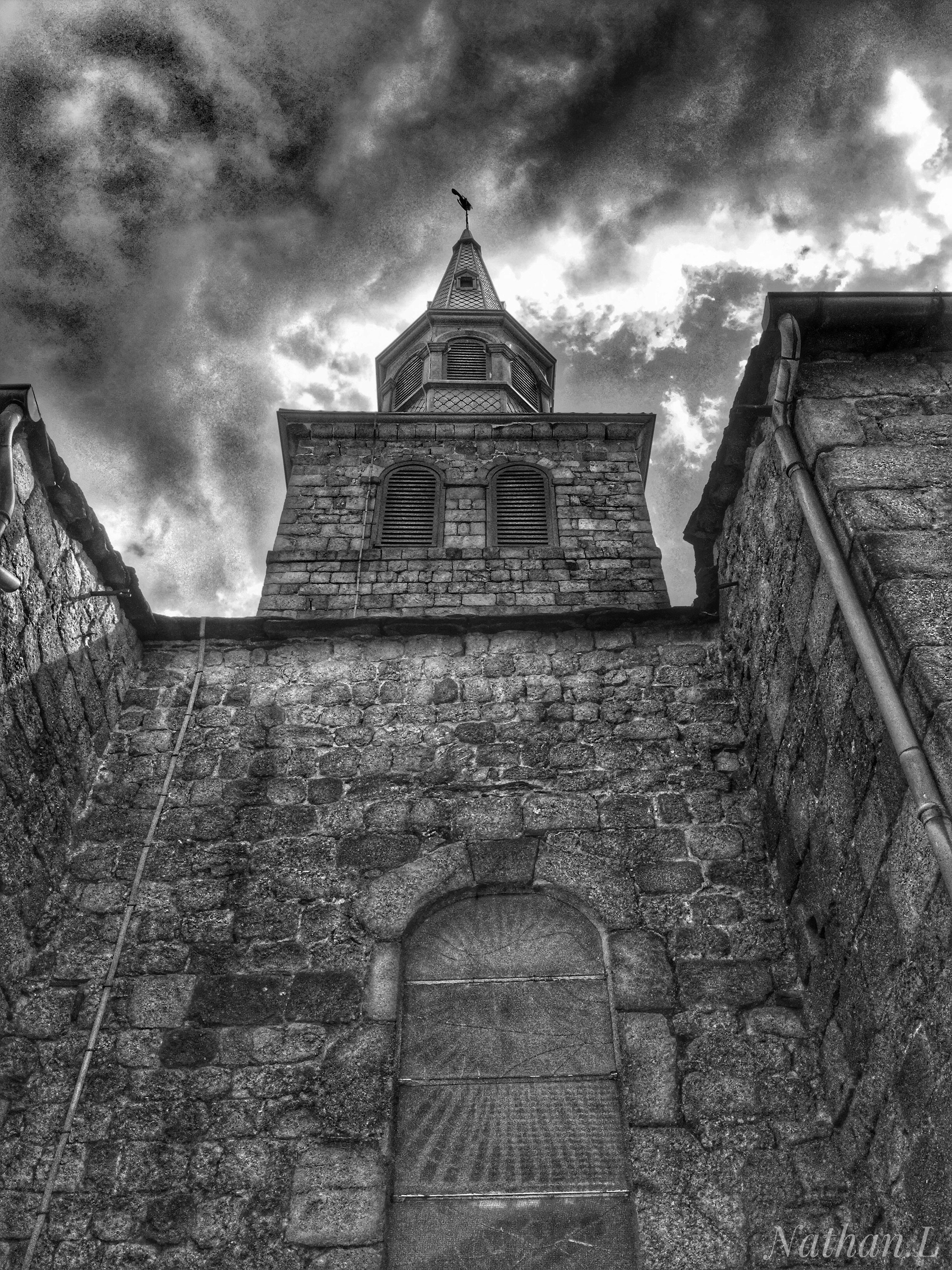 architecture, building exterior, built structure, low angle view, sky, cloud - sky, wall - building feature, cloud, wall, cloudy, outdoors, branch, storm cloud, day, spire, no people, place of worship, history, weathered, black and white