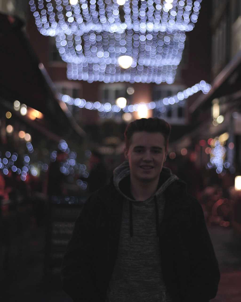 Portrait Of Smiling Man Standing Against Illuminated Decoration At Night