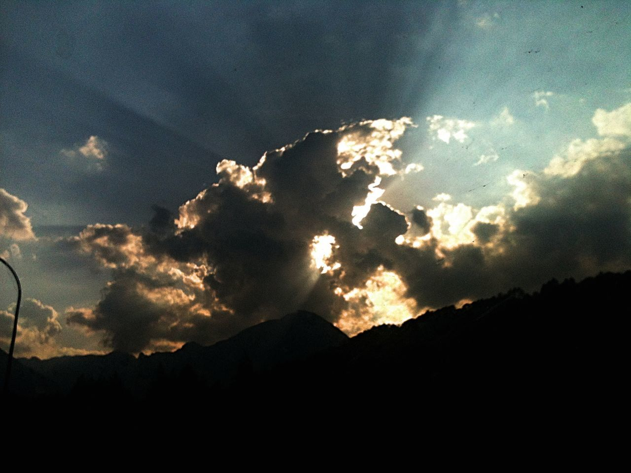 clouds cover the sun slowly makes its way, the sun's rays give a stage show. Beauty In Nature Cloud - Sky Day Dramatic Sky Low Angle View Nature No People Outdoors Scenics Silhouette Sky Sunbeam Sunset Tranquility EyeEmNewHere