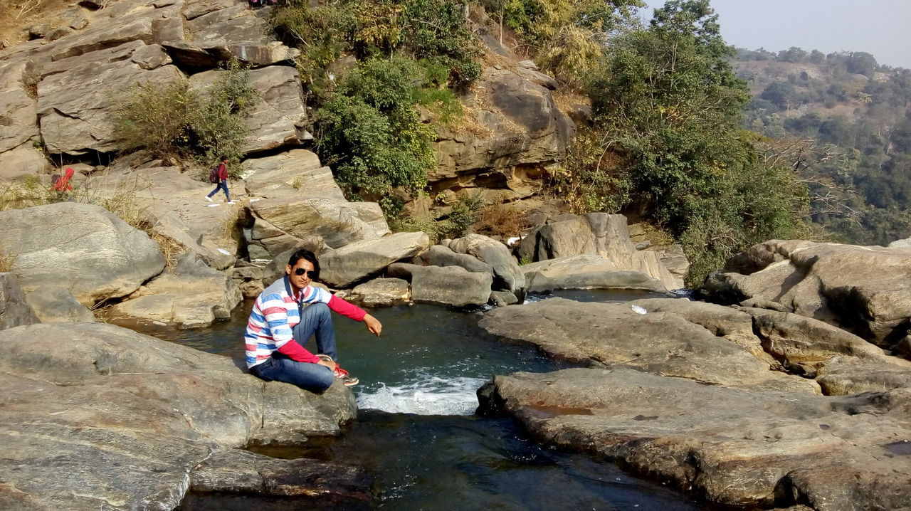 rock - object, one person, full length, adventure, river, leisure activity, childhood, day, casual clothing, outdoors, nature, cliff, mountain, one girl only, rock climbing, sitting, happiness, children only, people, tree, real people, water, waterfall, scenics, climbing, beauty in nature, child, rock face, young adult, adult