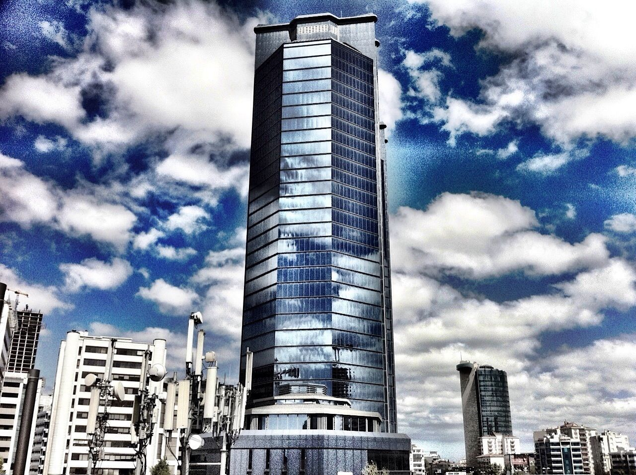 architecture, building exterior, skyscraper, built structure, tall - high, city, office building, tower, modern, low angle view, sky, building story, urban skyline, cloud, cityscape, tall, development, financial district, cloud - sky, outdoors, place of work, blue, growth, day, city life, capital cities, no people, downtown district
