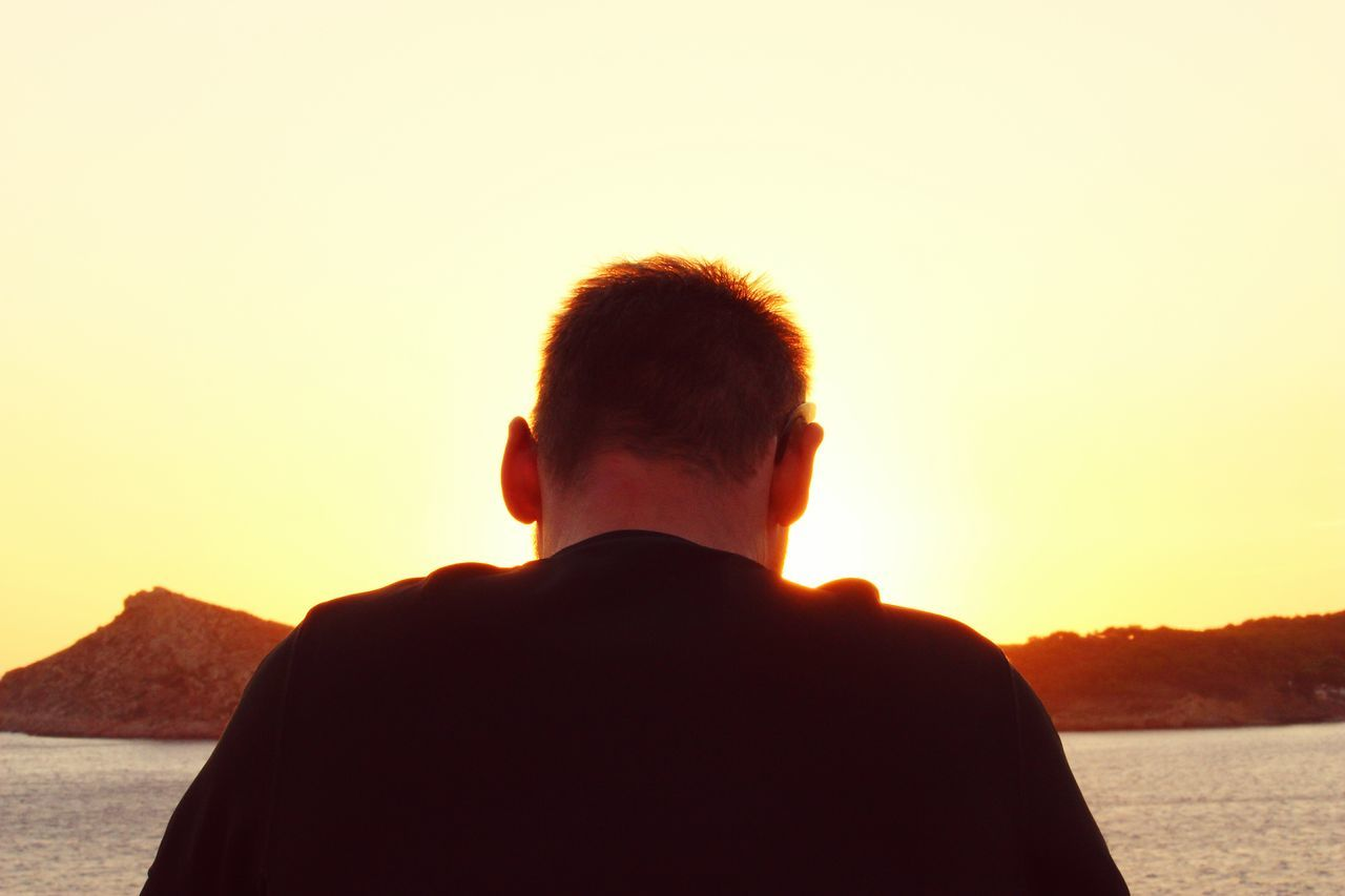 Rear View Of Man Against Sea During Sunset
