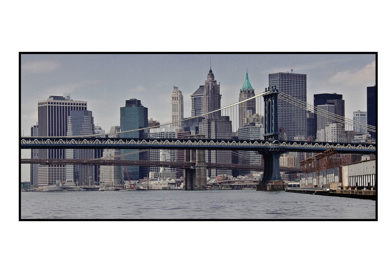 architecture, skyscraper, city, building exterior, built structure, urban skyline, cityscape, river, travel destinations, tower, modern, bridge - man made structure, no people, water, outdoors, skyline, day, connection, financial district, sky, city life, tall, downtown district, waterfront, clear sky
