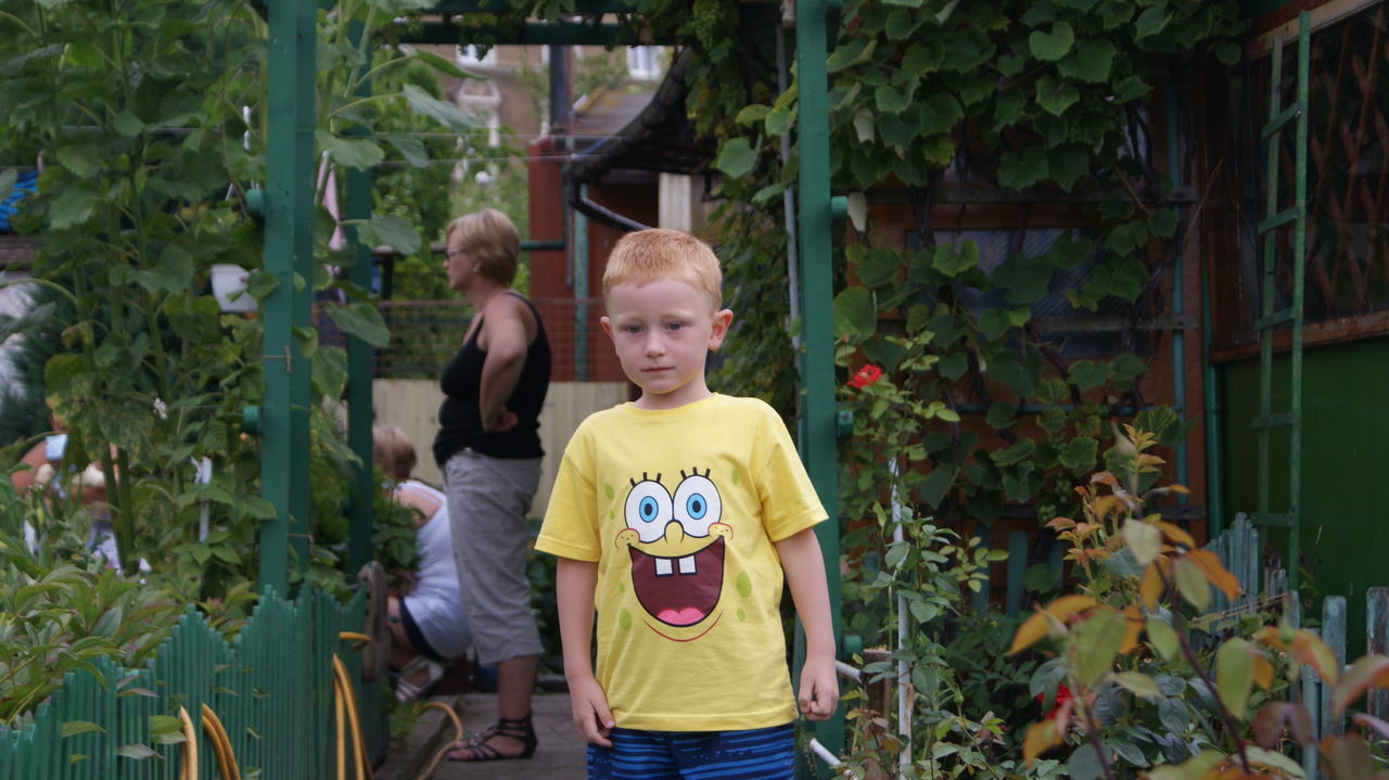 Portrait Of Boy Standing By Plants At Yard