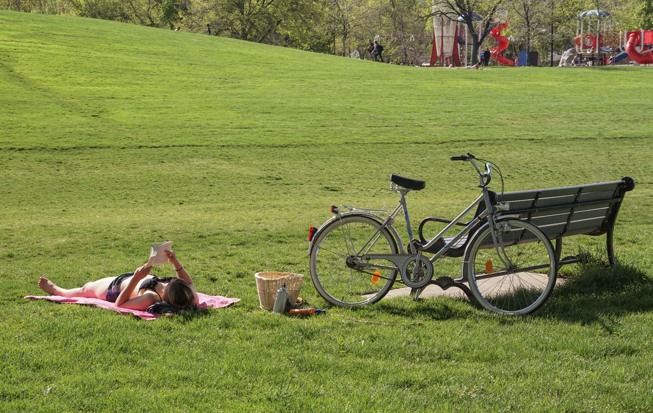 grass, bicycle, green color, lying down, lawn, leisure activity, field, day, nature, full length, vacations, outdoors, relaxation, beauty in nature, real people, one person, people, adult