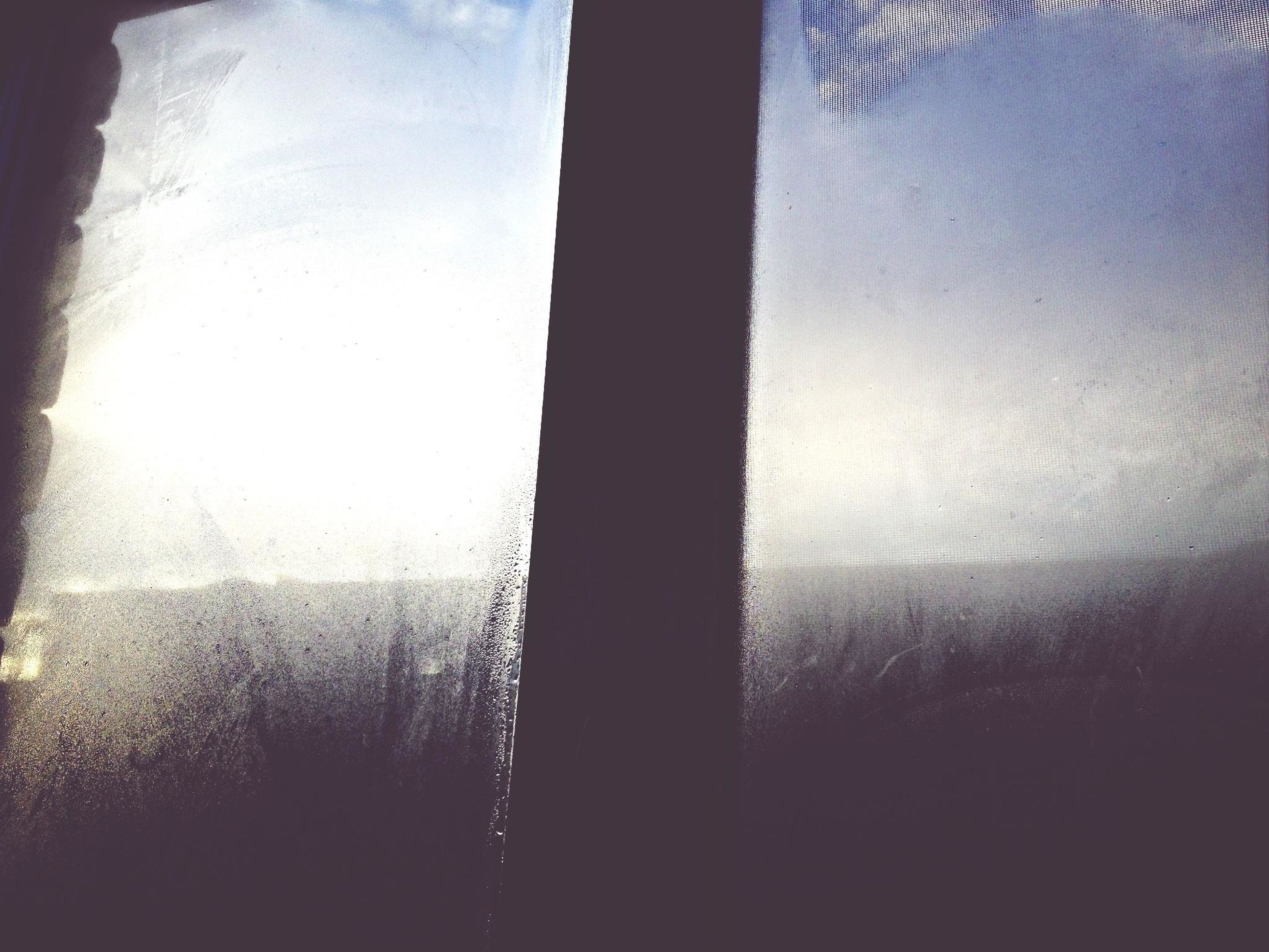 indoors, window, silhouette, glass - material, transparent, sunlight, dark, auto post production filter, sky, transfer print, shadow, no people, reflection, day, curtain, close-up, looking through window, built structure, nature, dusk