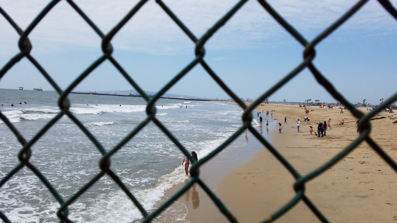 chainlink fence, sea, day, protection, safety, nature, beach, travel destinations, real people, water, outdoors, sky, vacations, large group of people, beauty in nature, people