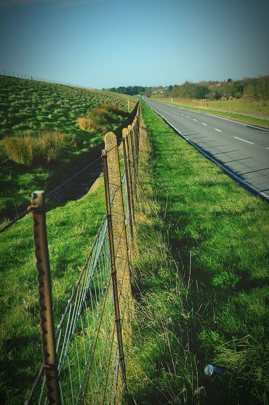 Open Road No Traffic Road Country Road Roadside Grass Verge Green Grass Fence Fence Post Fence Posts Metal Fence Concrete Litter Drink Can Perspective Countryside From My Point Of View Blue Sky United Kingdom Nikon D3200