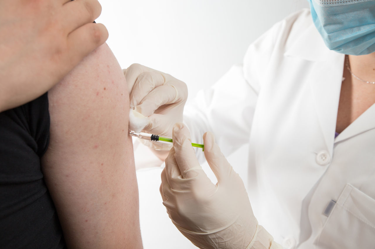 Close up of a female doctor or nurse giving an injection or vaccine to a male patient Adult AlleViate Doctor  Drug Grip Hospital Injection Latin Nurse Serum Woman Antiseptic Cure Dose Equipment Face Female Flu Girl Healthy Eating Inoculation Medical Syringe Vaccination Young Adult