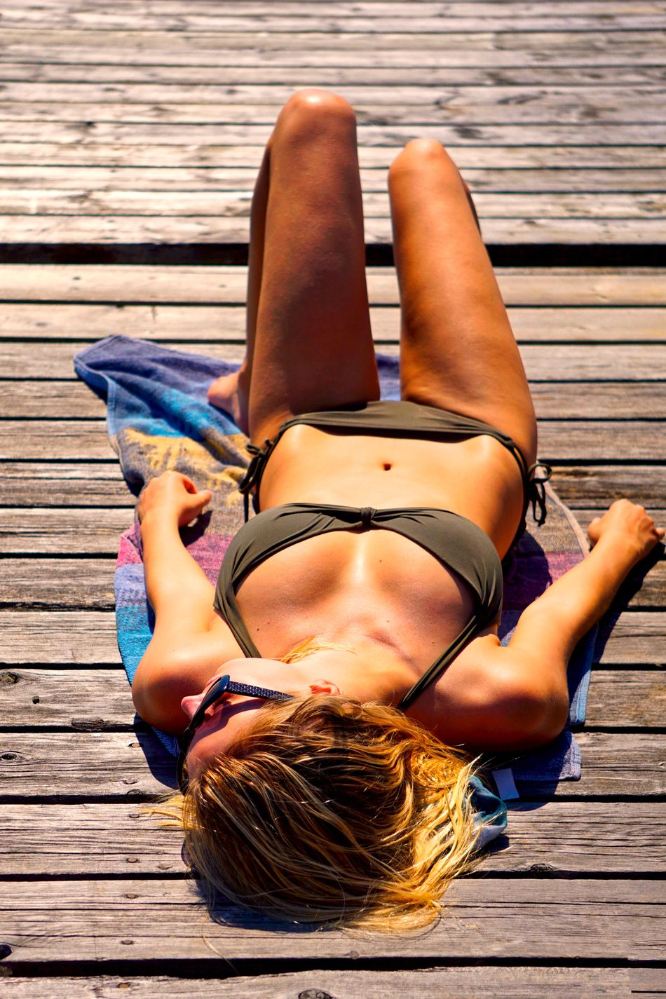 Young woman lying on dock on a towel sunbathing Adult Bikini Cottage Life Day Dock Full Length High Angle View Leisure Activity Lifestyles Lying Down Lying On Back One Person Outdoors Pier Real People Relaxation Sunbathing Suntanning Towel Vacations Water Wood - Material Young Adult Young Woman