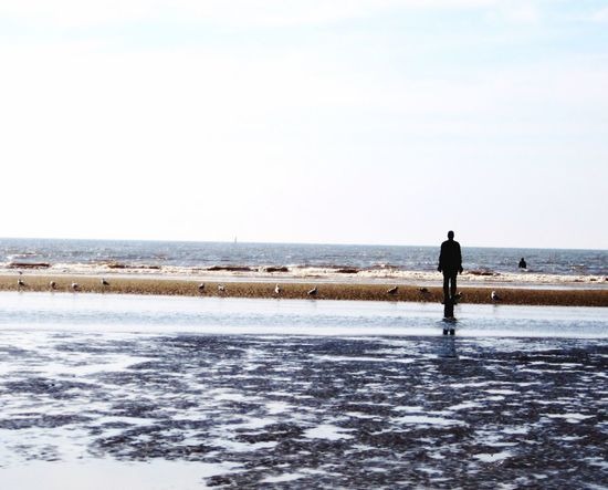 Liverpool Crosby Beach Another Place By Anthony Gormley Water Nature Full Length Horizon Over Water Beach Beauty In Nature Scenics Tranquil Scene Walking Rear View One Person Tranquility Clear Sky Outdoors Day Lifestyles Men Perspectives On Nature