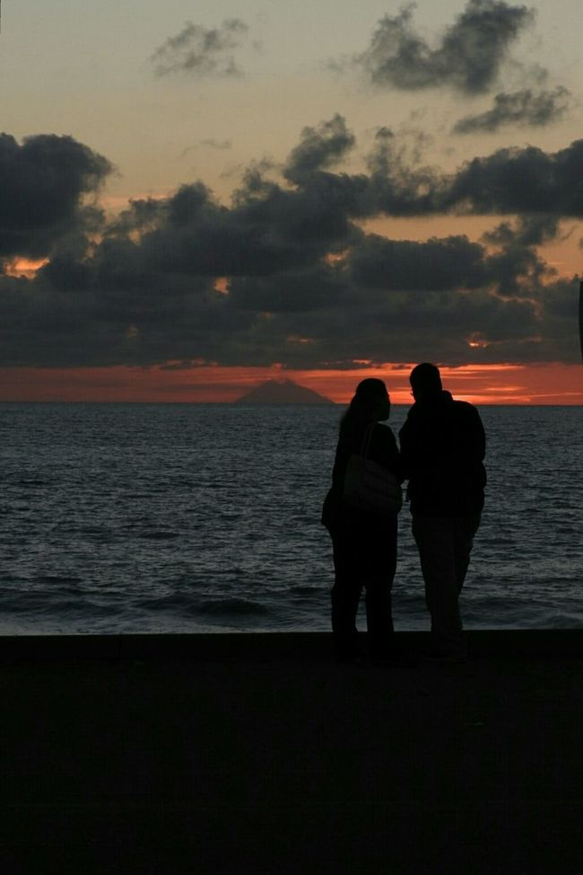 The sea, sunsent and lovers... Horizon Over Water Sea Silhouette Water Sunset Standing Tranquil Scene Sky Orange Sunset Taking Photos Taking Pictures Orange Color Lovers On The Sun ☀ Silhouettes Of People Silhouette Photography