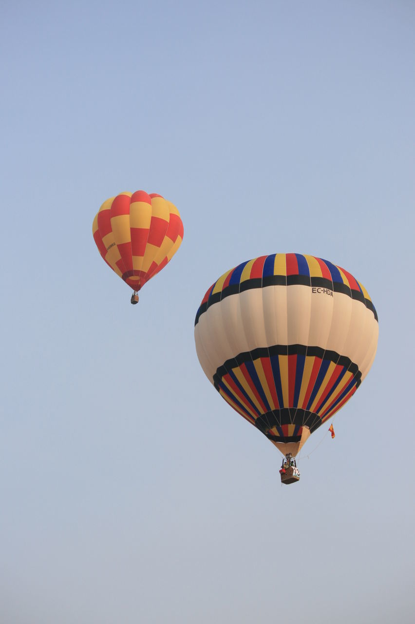 adventure, low angle view, flying, mid-air, multi colored, hot air balloon, copy space, parachute, clear sky, extreme sports, transportation, outdoors, day, sky, ballooning festival, nature, no people