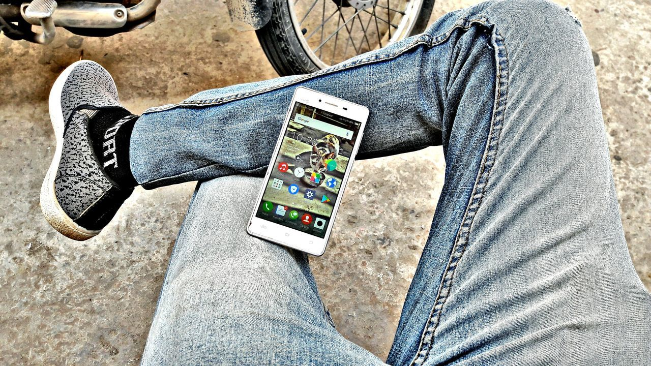 jeans, casual clothing, communication, wireless technology, one person, human body part, portable information device, smart phone, one man only, technology, men, midsection, only men, low section, mobile phone, human leg, day, portability, outdoors, adult, lifestyles, adults only, close-up, people, human hand, young adult