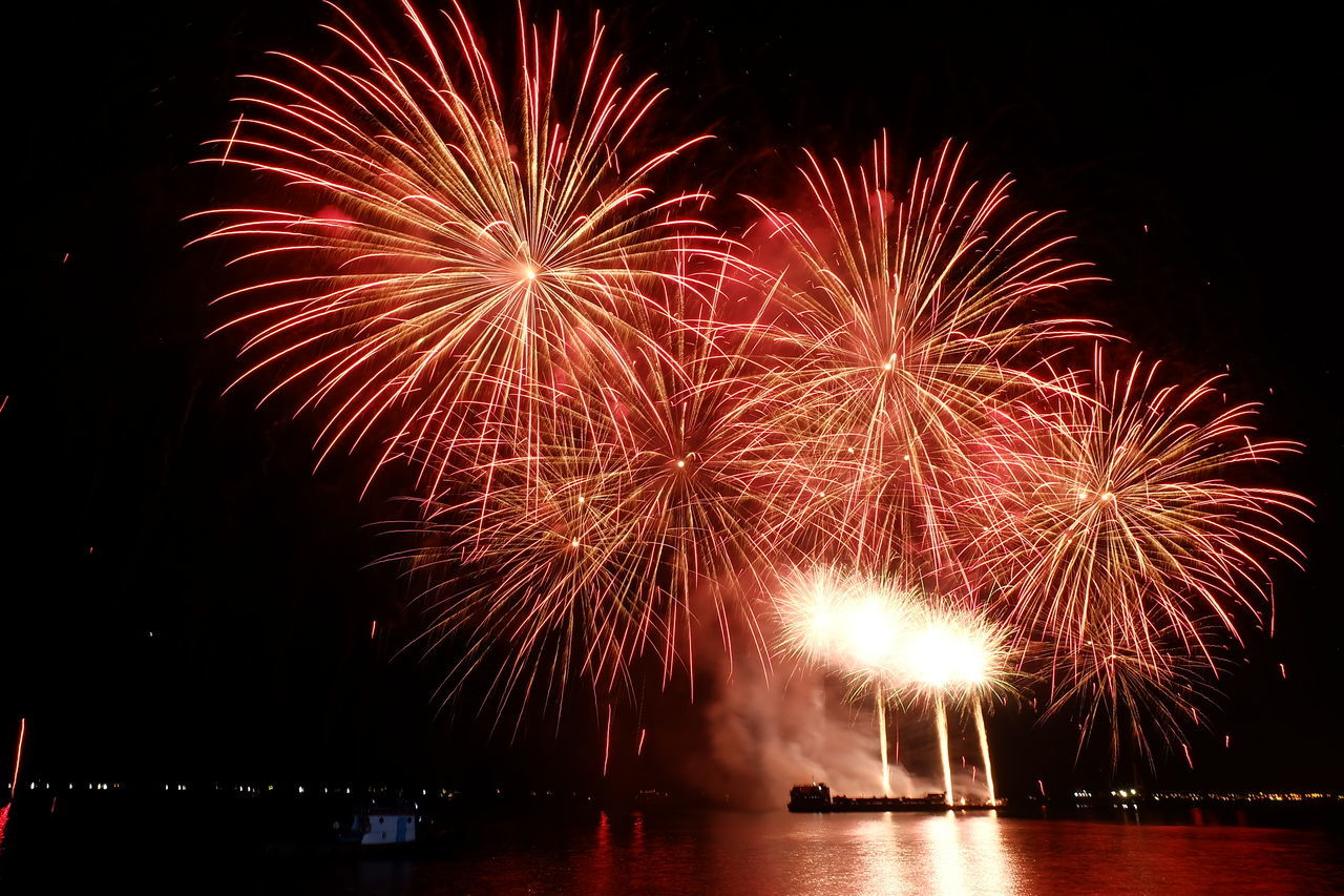 firework display, night, celebration, firework - man made object, exploding, illuminated, arts culture and entertainment, event, long exposure, water, river, waterfront, sky, multi colored, no people, firework, outdoors, low angle view