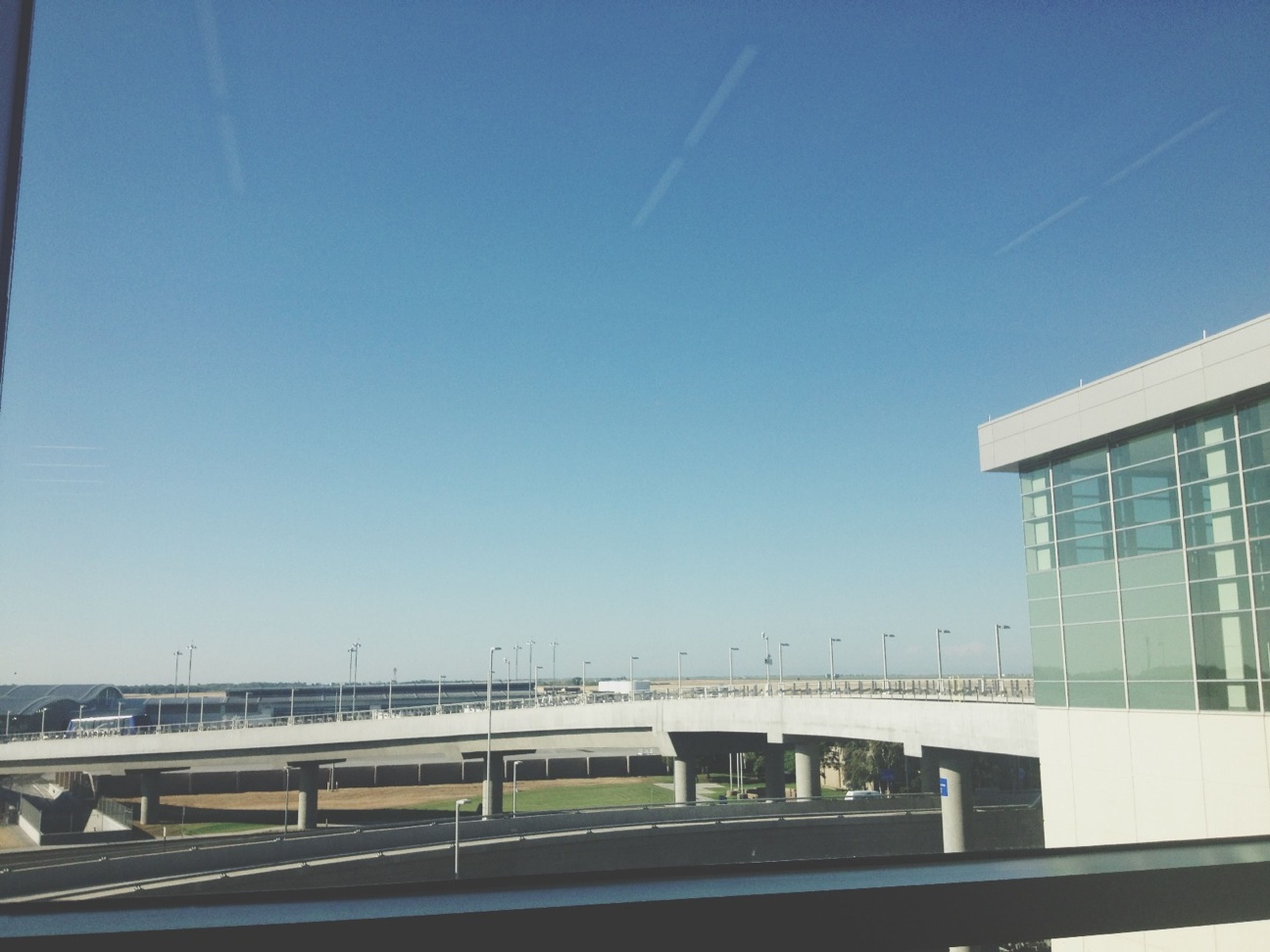 architecture, built structure, clear sky, building exterior, copy space, transportation, blue, city, connection, bridge - man made structure, railing, low angle view, modern, bridge, glass - material, building, road, day, sky, window