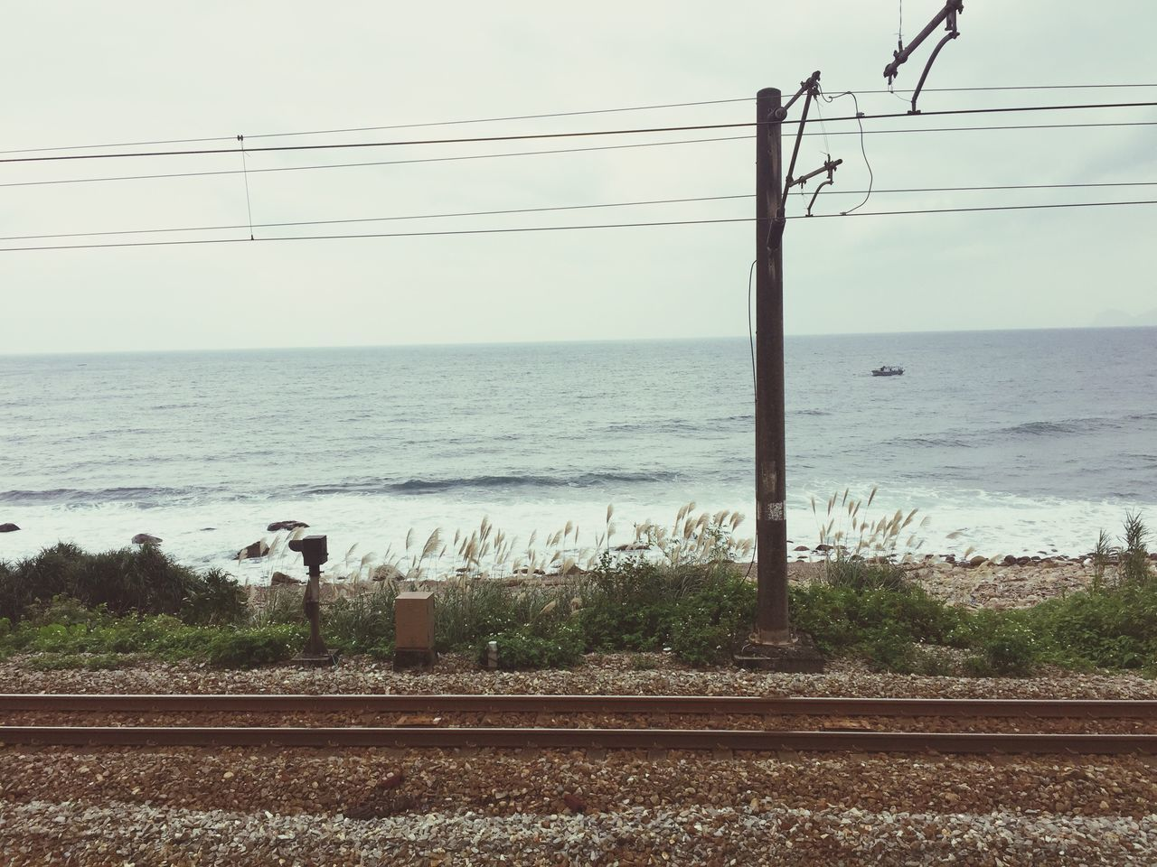 cable, railroad track, power line, rail transportation, transportation, sea, sky, connection, electricity pylon, water, electricity, nature, technology, day, outdoors, power supply, clear sky, no people, scenics, horizon over water, beauty in nature