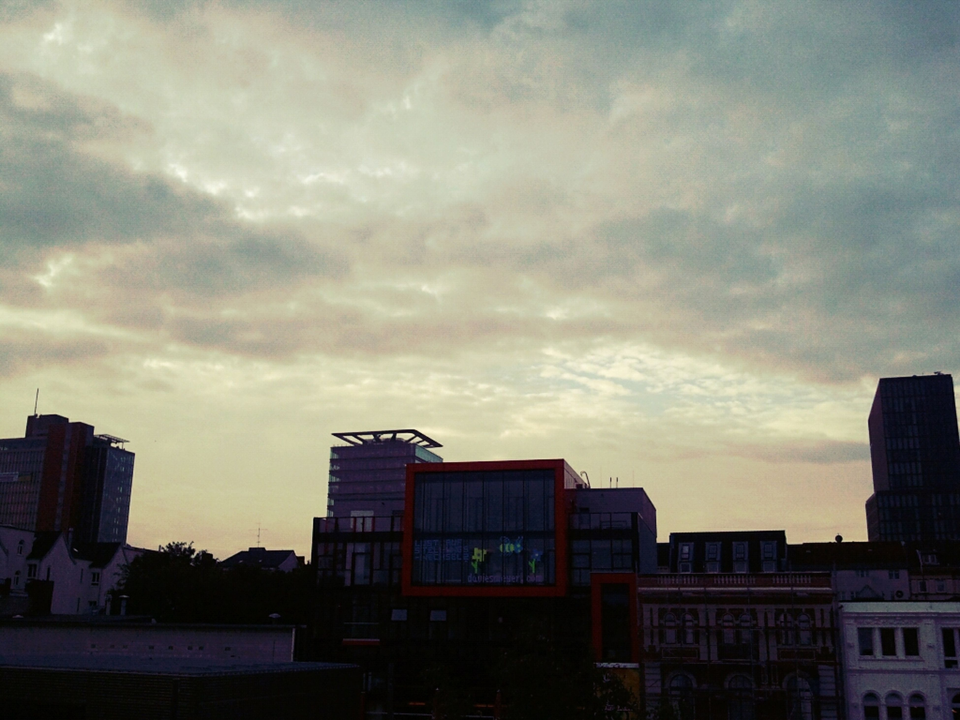 building exterior, architecture, built structure, sky, city, cloud - sky, sunset, cloudy, building, residential building, low angle view, cloud, residential structure, cityscape, skyscraper, city life, weather, modern, dusk, overcast