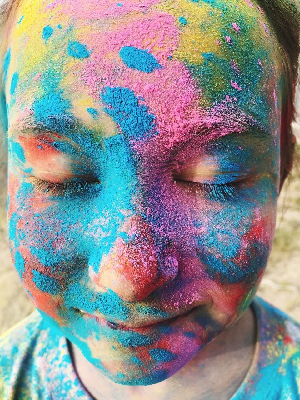 Close-Up Of Woman With Colorful Powder Paint On Face During Holi