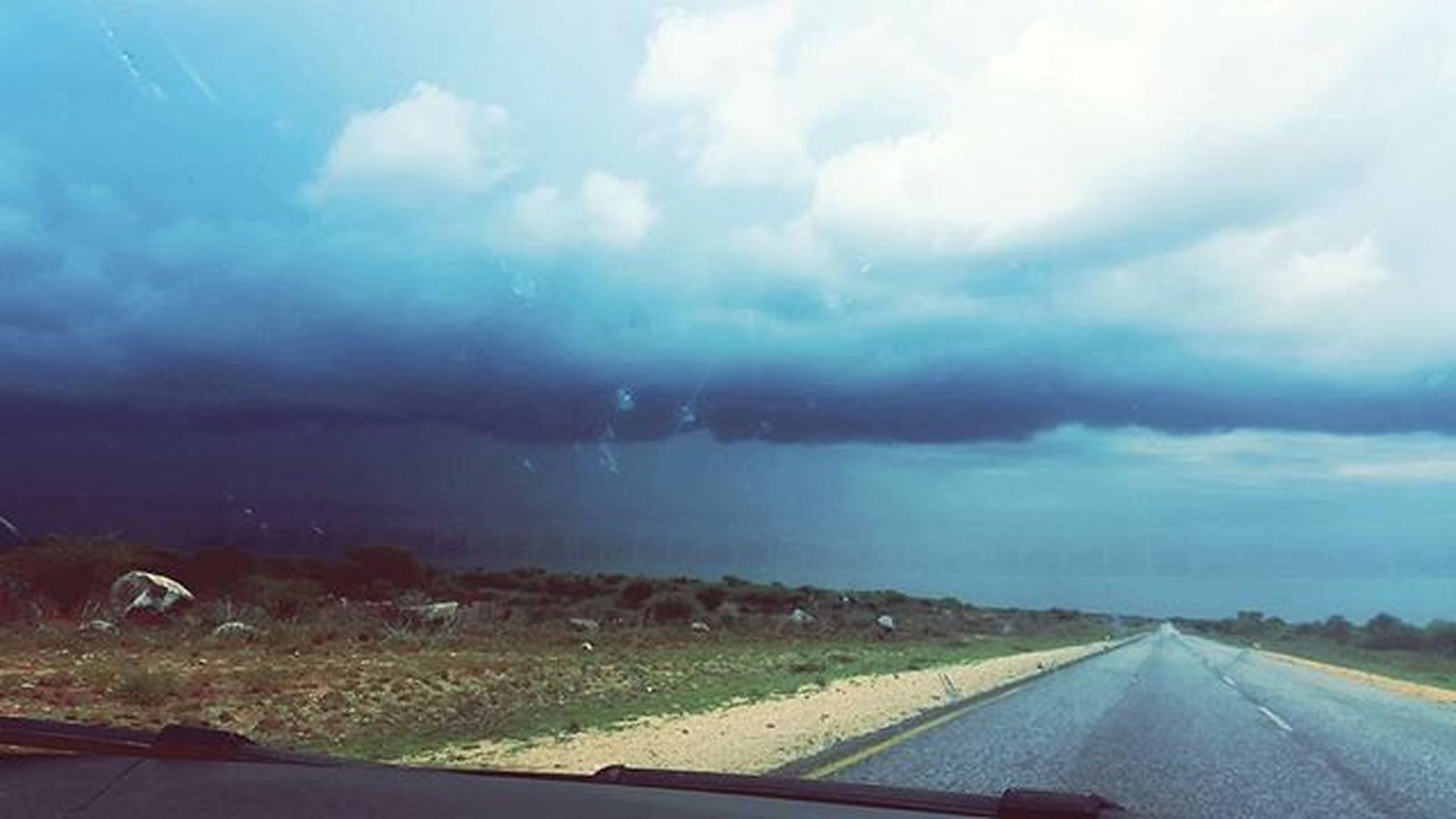 sky, cloud - sky, transportation, road, cloudy, landscape, the way forward, cloud, nature, weather, tranquil scene, scenics, tranquility, road marking, beauty in nature, overcast, field, country road, car, storm cloud