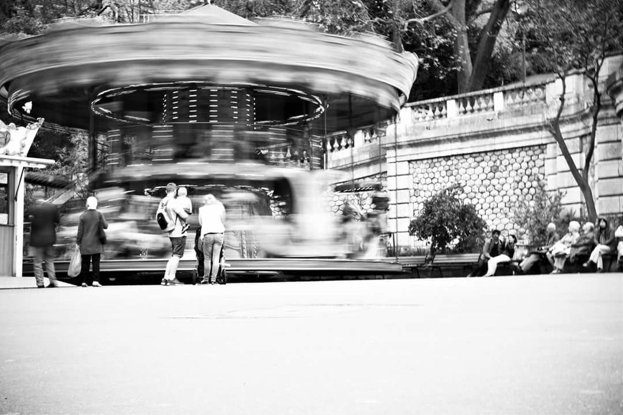 leisure activity, blurred motion, real people, arts culture and entertainment, amusement park, large group of people, motion, carousel, enjoyment, men, lifestyles, outdoors, women, day, amusement park ride, merry-go-round, adult, people