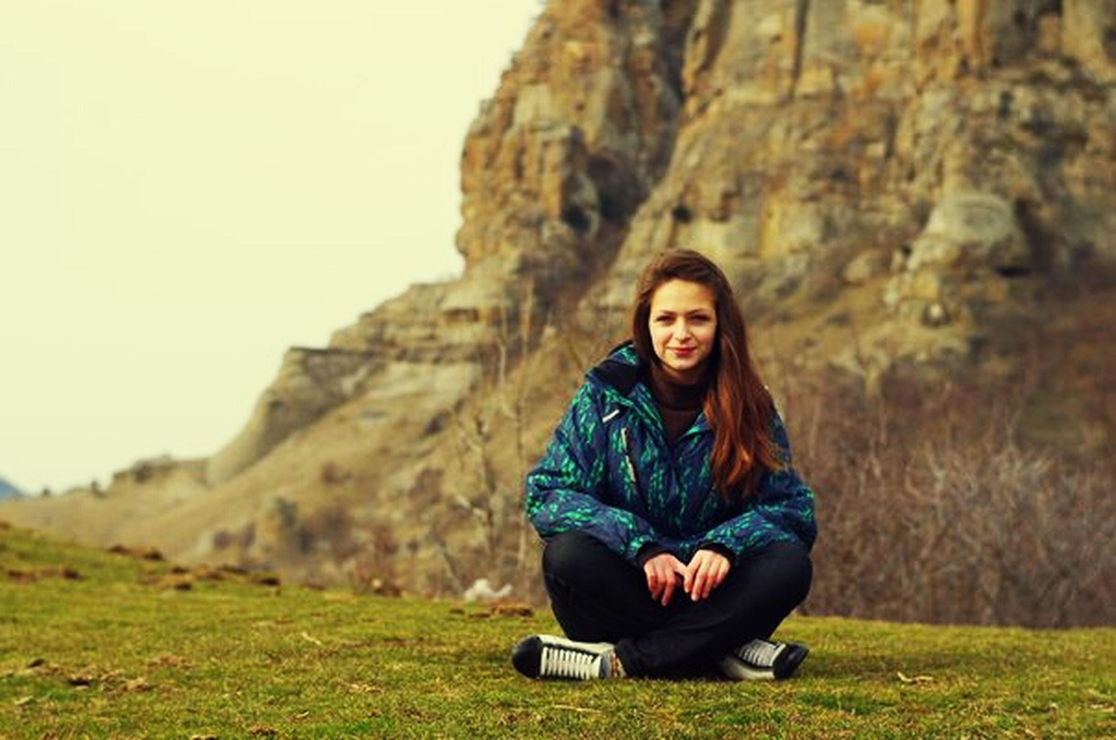 lifestyles, casual clothing, leisure activity, young adult, person, looking at camera, smiling, portrait, mountain, young women, grass, sitting, front view, full length, landscape, three quarter length