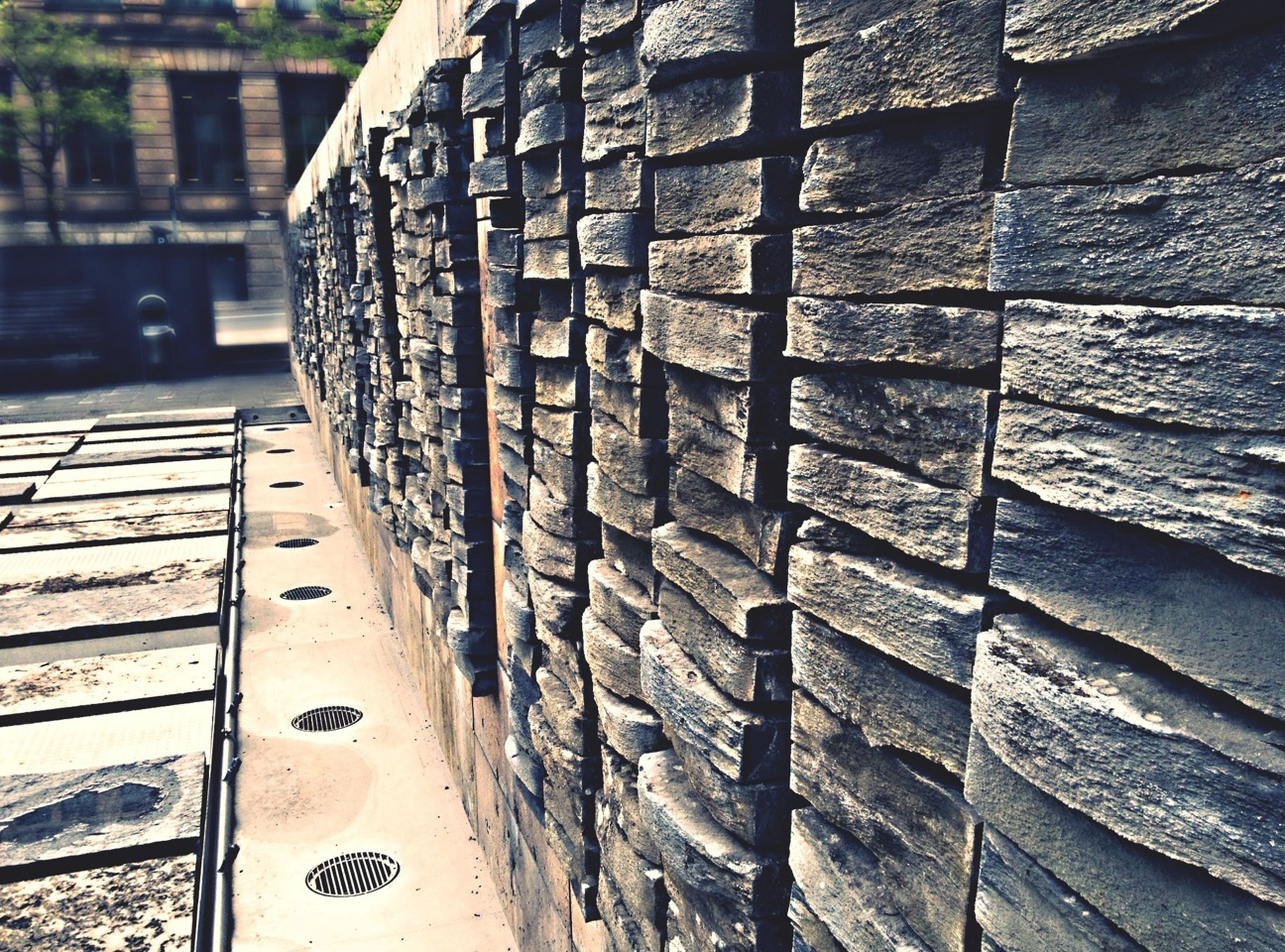 close-up, focus on foreground, transportation, textured, day, street, outdoors, wall - building feature, part of, cropped, metal, sidewalk, weathered, no people, sunlight, pattern, built structure, building exterior, wood - material, brick wall