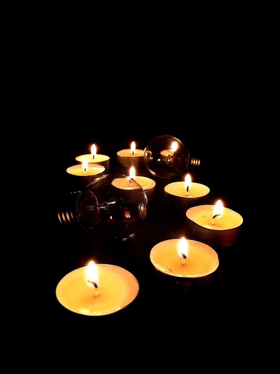 Close-Up Of Lit Candles And Light Bulb