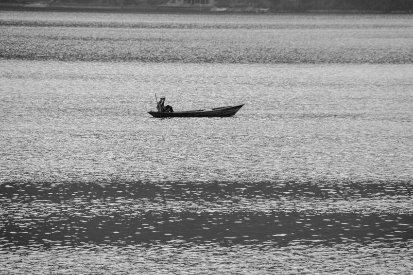 Transportation Mode Of Transport Water Nature Day Real People Nautical Vessel Silhouette Outdoors Beach Beauty In Nature Solitary Moments Copy Space Minimalism One Man In A Boat Boating In The Lake