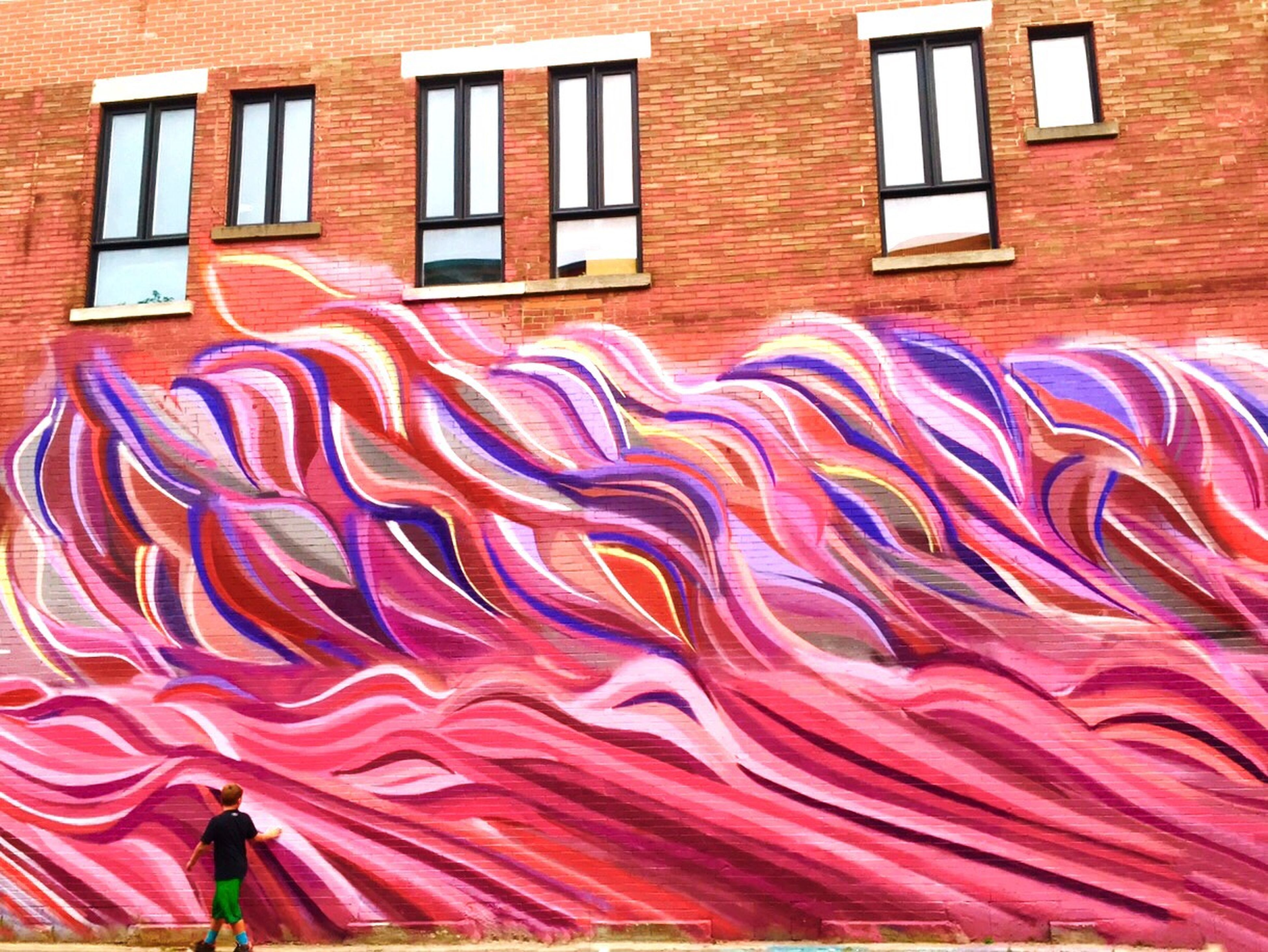 building exterior, architecture, built structure, red, multi colored, window, wall - building feature, art and craft, clothing, building, outdoors, lifestyles, day, pattern, leisure activity, brick wall, creativity, art