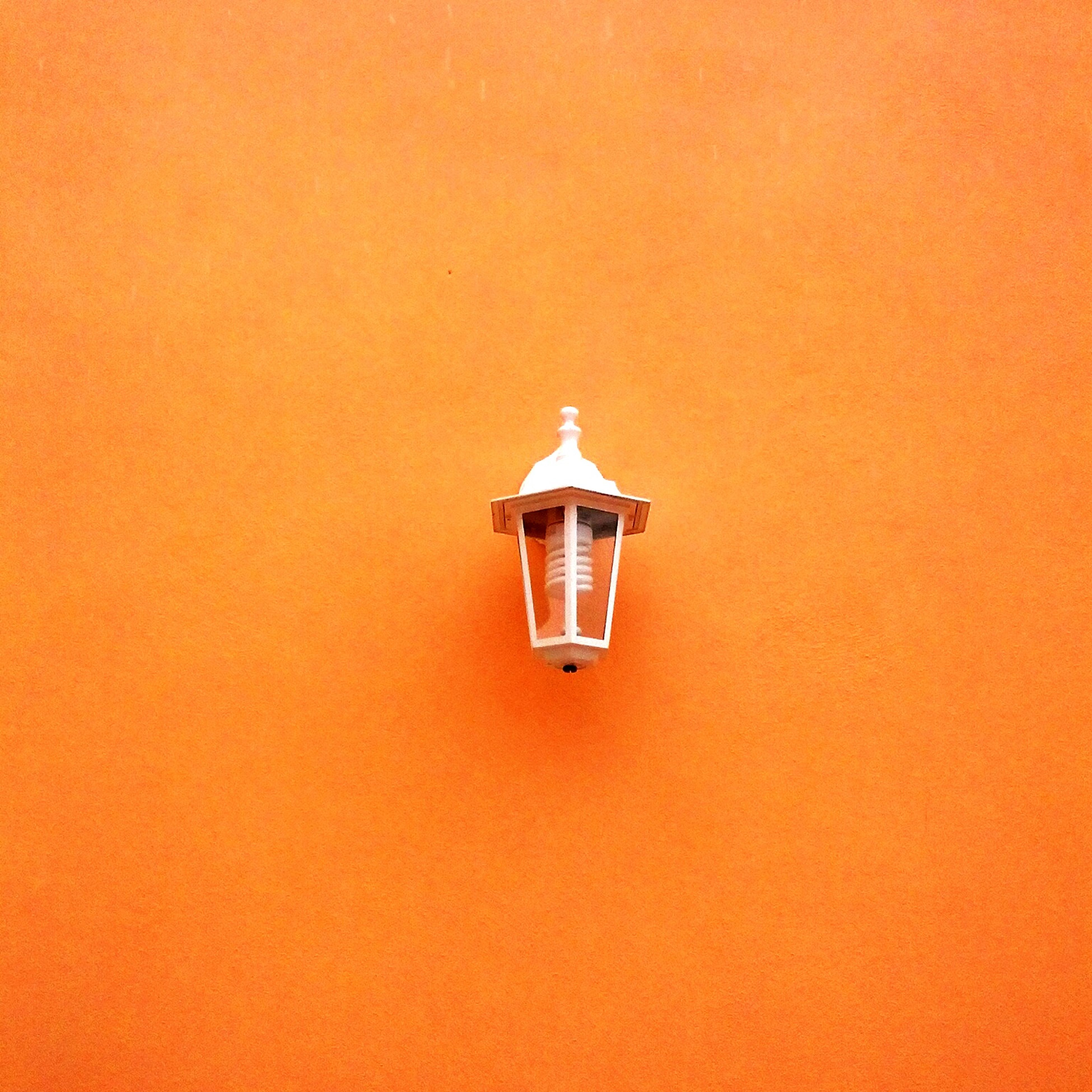 lighting equipment, copy space, low angle view, illuminated, electricity, wall - building feature, indoors, lamp, electric light, orange color, built structure, electric lamp, light bulb, lantern, close-up, single object, architecture, hanging, no people, wall
