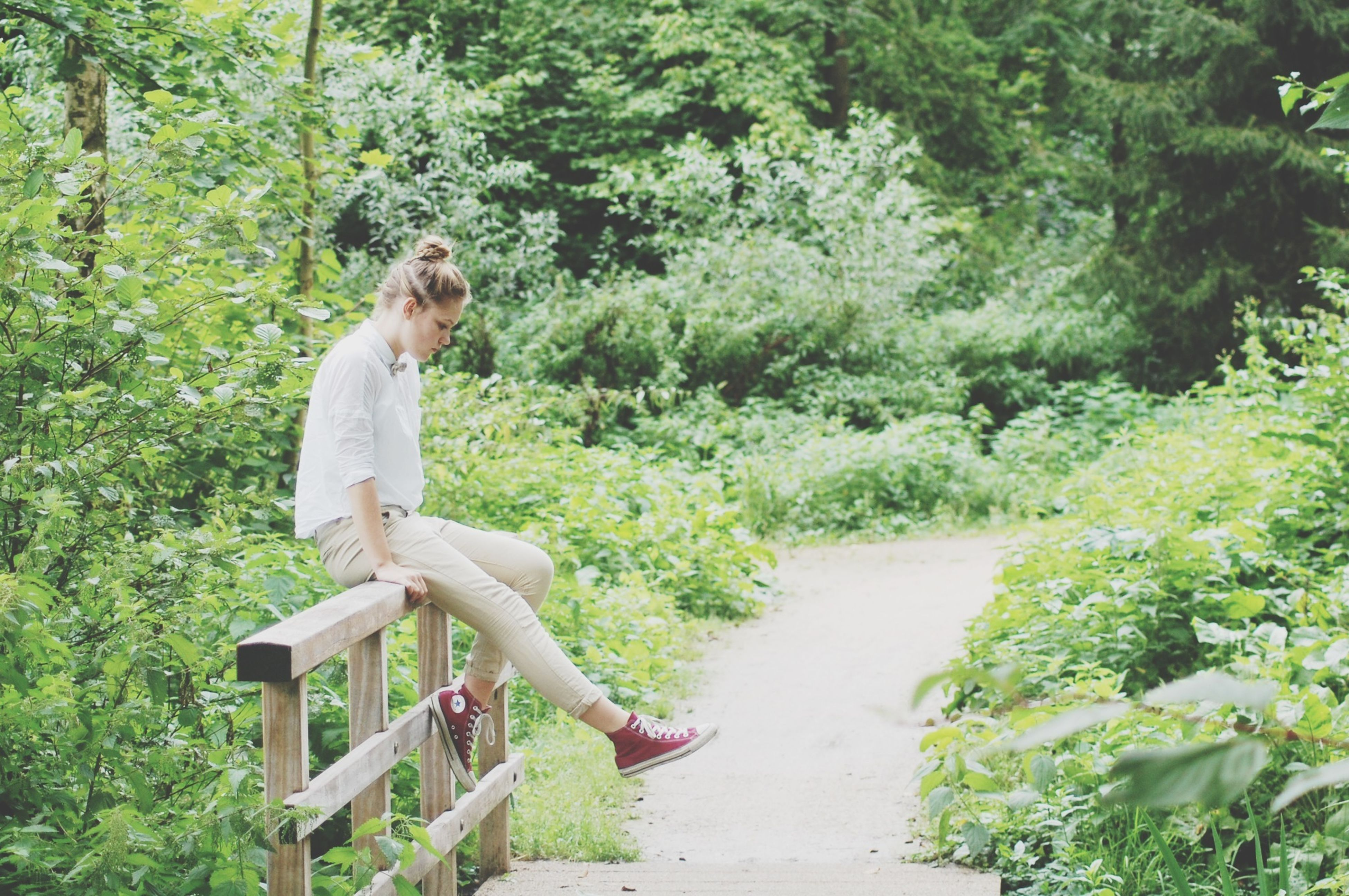 full length, tree, lifestyles, leisure activity, green color, casual clothing, person, young adult, growth, plant, jumping, side view, sitting, nature, park - man made space, animal themes, day, outdoors