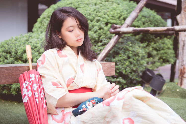 Beautiful Woman Black Hair Building Exterior Day Grass Kimono Long Hair Nature One Person Outdoors Park - Man Made Space People Real People Relaxation Sitting Young Adult Young Women